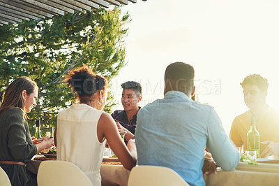 Buy stock photo Rearview shot of a group of friends enjoying a meal and drinks  together around a table at a gathering outdoors