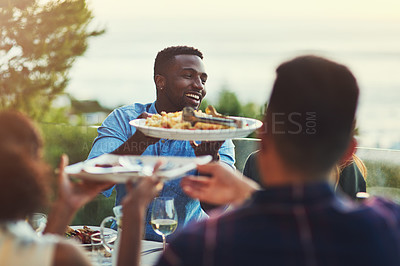 Buy stock photo Shot of a handsome young man passing a plate of pasta around at a gathering with friends outdoors
