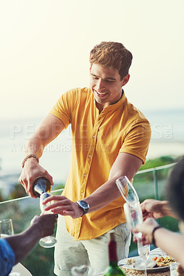 Buy stock photo Shot of a handsome young man pouring a bottle of champagne while his friends hold up their glasses outdoors