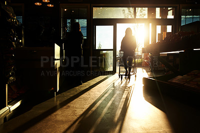 Buy stock photo Cropped shot of a woman walking into a grocery store and pushing a shopping cart