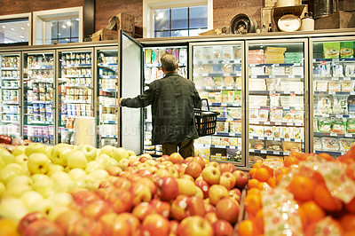 Buy stock photo Shot of a mature man shopping in the cold produce section of a supermarket