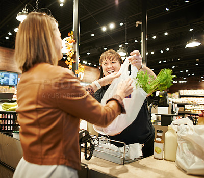 Buy stock photo Shot of a cashier handing a customer her shopping bag at a supermarket