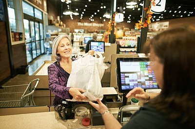 Buy stock photo Shot of a mature woman taking a shopping bag from the cashier at a supermarket