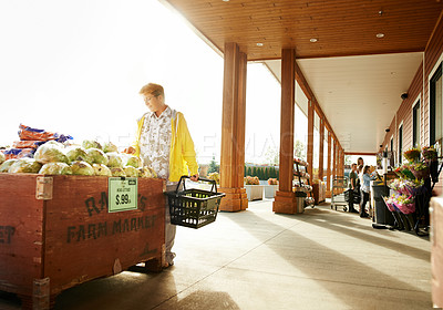 Buy stock photo Shot of a mature woman shopping for fresh produce outside at a supermarket