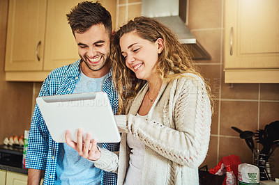 Buy stock photo Cropped shot of a loving couple using a digital tablet together at home