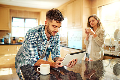 Buy stock photo Shot of a young man using a digital tablet with his girlfriend standing in the background