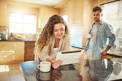 Buy stock photo Shot of a young woman using a digital tablet with her boyfriend standing in the background