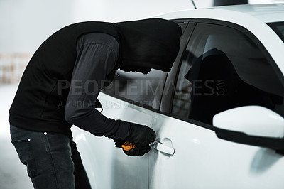 Buy stock photo Shot of a masked criminal picking the lock of a car door inside a parking lot