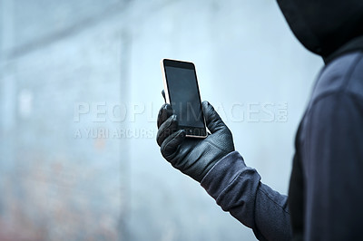 Buy stock photo Shot of a male burglar using his phone outdoors
