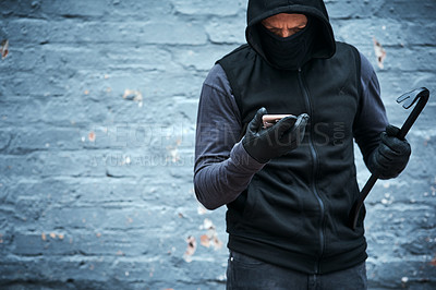 Buy stock photo Shot of a male burglar holding a steel weapon and using his phone outdoors