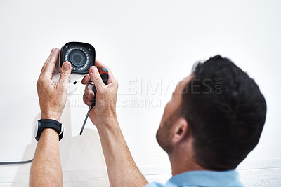 Buy stock photo Shot of a mature man installing a security camera on a building