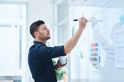 Buy stock photo Shot of a handsome mature male designer working on a whiteboard in the office