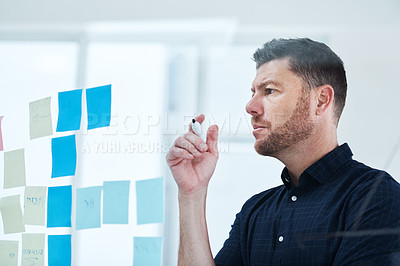 Buy stock photo Shot of a handsome mature businessman working on a glass wipe board in his office