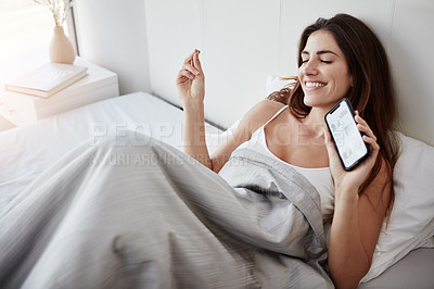 Buy stock photo Shot of a beautiful young woman snapping her fingers while holding her cellphone in bed