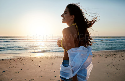 Buy stock photo Shot of a beautiful young woman enjoying herself at the beach at sunset