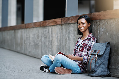 Buy stock photo Full length portrait of an attractive young female student reading a book while sitting outside on campus