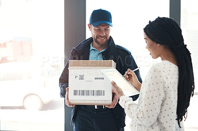 Buy stock photo Shot of a handsome delivery man getting a signature from a female customer for her order