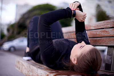 Buy stock photo Full length shot of an attractive young woman checking the time while taking a break from her run on the promenade