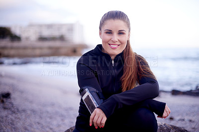 Buy stock photo Cropped portrait of an attractive young woman taking a break from her workout on the beach