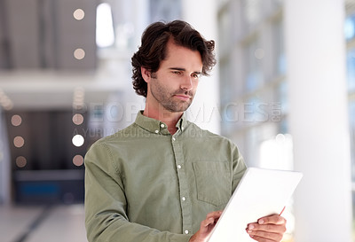 Buy stock photo Shot of a young businessman using a digital tablet in a modern office