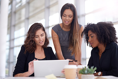 Buy stock photo Shot of a group of young businesswomen using a digital tablet during a meeting in a modern office