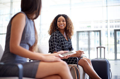 Buy stock photo Cropped shot of an attractive young businesswoman talking to a fellow female professional while sitting in an airport departure lounge