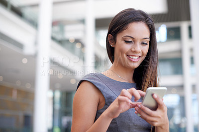 Buy stock photo Cropped shot of an attractive young businesswoman sending text messages while standing in her office