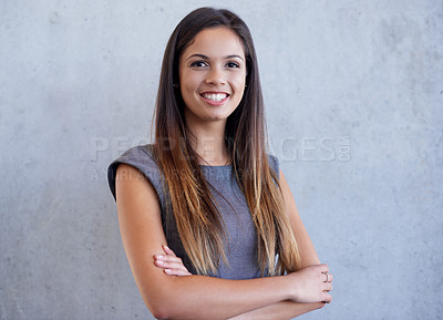 Buy stock photo Studio portrait of an attractive young businesswoman standing with her arms folded against a grey background