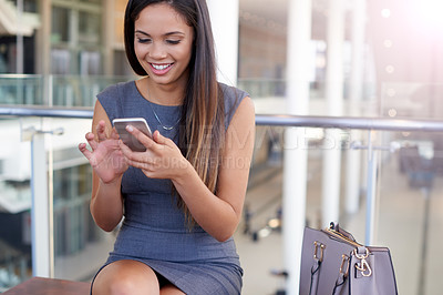 Buy stock photo High angle shot of an attractive young businesswomen sending a text message in the office
