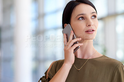 Buy stock photo Cropped shot of an attractive young businesswoman making a phonecall while standing in the office