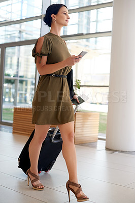 Buy stock photo Full length shot of an attractive young businesswoman sending a text message while walking through an airport terminal