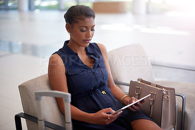 Buy stock photo High angle shot of an attractive young businesswomen using her tablet while sitting in the office