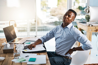 Buy stock photo Shot of a young businessman suffering from back pain while trying to work in the office