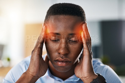 Buy stock photo Shot of a young and stressed businessman suffering from a headache while trying to work in the office