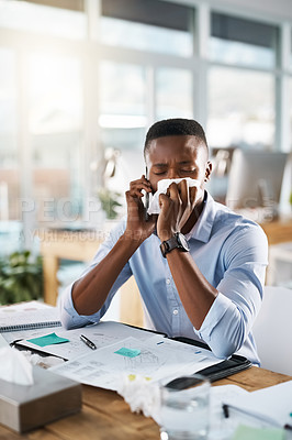 Buy stock photo Shot of a sickly young businessman taking a phone call while covering his nose with a tissue in his office