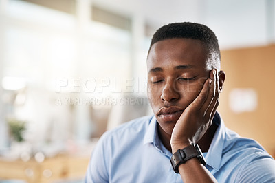Buy stock photo Shot of an exhausted young businessman taking a quick nap on his hand at work