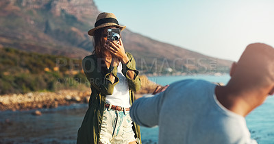 Buy stock photo Cropped shot of a happy young woman photographing her boyfriend at the beach