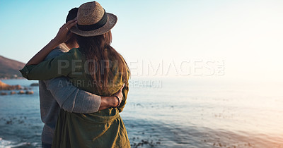 Buy stock photo Rearview shot of an affectionate young couple embracing each other on the beach at sunset