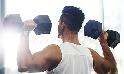 Buy stock photo Rearview shot of a young man working out with dumbbells in a gym