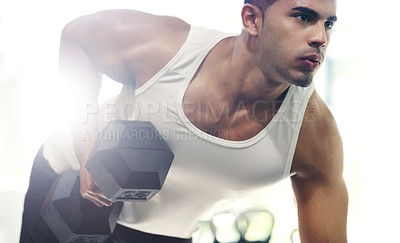 Buy stock photo Cropped shot of a focused young sportsman working out with dumbbells in the gym