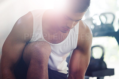 Buy stock photo Cropped shot of a focused young sportsman tying his shoelaces in a gym