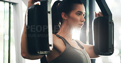 Buy stock photo Cropped shot of a focused young woman working out on an exercise machine in a gym