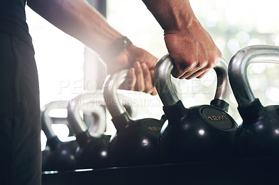 Buy stock photo Cropped shot of an unrecognizable sportsman working out with kettlebells in a gym