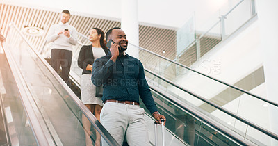 Buy stock photo Cropped shot of a businessman talking on a mobile phone while on an escalator