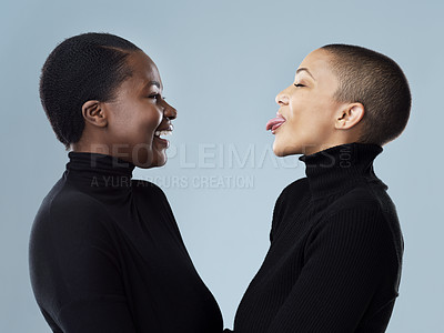 Buy stock photo Studio shot of two beautiful young women pulling faces to each other while standing against a grey background