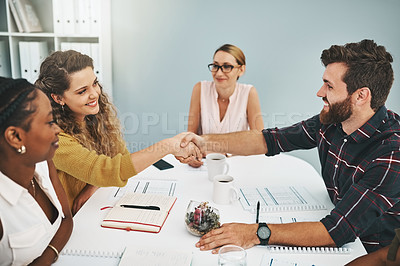 Buy stock photo Cropped shot of two young designers shaking hands during a meeting in the boardroom