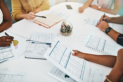 Buy stock photo High angle shot of a group of unrecognizable designers sitting in the boardroom during a meeting