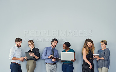 Buy stock photo Studio shot of a group of businesspeople using their wireless devices while waiting in a line and talking to each other