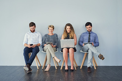 Buy stock photo Studio shot of a group of businesspeople using their wireless devices while being seated and waiting in a line