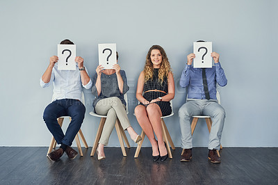 Buy stock photo Studio shot of a group of businesspeople holding up speech bubbles with question marks in them while being seated